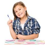 La muchacha está escribiendo en etiquetas engomadas del color usando pluma Fotografía de archivo libre de regalías