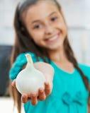 La muchacha está sosteniendo la cebolla Fotografía de archivo libre de regalías