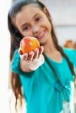 La muchacha está sosteniendo la manzana Foto de archivo libre de regalías