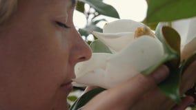 La muchacha est? sosteniendo las flores blancas hermosas de la magnolia en sus manos almacen de video