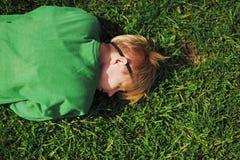 La muchacha estaba cansada y coloca para relajarse en la hierba cerca del camino Imagenes de archivo