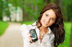 La muchacha estira el teléfono móvil Imagenes de archivo