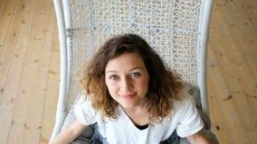 La muchacha europea joven en un vestido de lino balancea en un hamaca-oscilación en un apartamento del desván y mira para arriba  almacen de metraje de vídeo