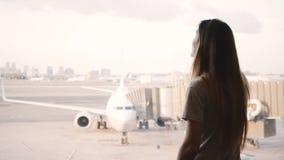 La muchacha europea joven habla en smartphone y las sonrisas, extremos llaman en la ventana terminal de aeropuerto, aeroplano en  almacen de video
