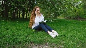La muchacha europea lanza la parte posterior larga del pelo rizado y lee un libro en la naturaleza, movimiento de la cámara Recli almacen de metraje de vídeo