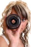 La muchacha examina el lense Imagen de archivo libre de regalías