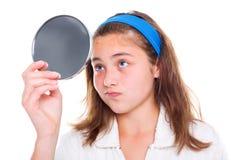 La muchacha examina sus espinillas en el espejo Imagen de archivo libre de regalías