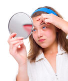 La muchacha examina sus espinillas en el espejo Fotografía de archivo libre de regalías