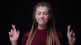 La muchacha excéntrica con la perforación y dreadlocks cierra ojos y hace que los cruzar-fingeres firman para mostrar esperanza y almacen de video
