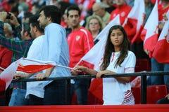 La muchacha-fan de Sevilla FC permanece en los soportes con una bandera Imagen de archivo libre de regalías