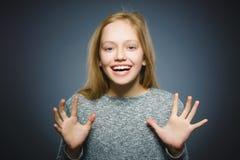 La muchacha feliz acertada del retrato del primer aisló el fondo gris Imagenes de archivo