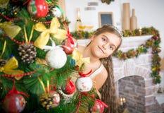 La muchacha feliz adorna el árbol de navidad Imagen de archivo libre de regalías