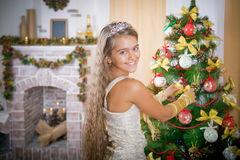 La muchacha feliz adorna el árbol de navidad Imagen de archivo