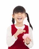 La muchacha feliz ahorra el dinero con la hucha Foto de archivo libre de regalías