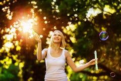 La muchacha feliz alegre con sonrisa hermosa está soplando burbujas Fotografía de archivo libre de regalías