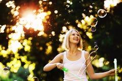 La muchacha feliz alegre con sonrisa hermosa está soplando burbujas Fotos de archivo libres de regalías