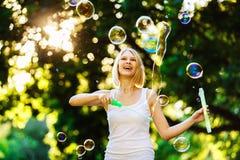 La muchacha feliz alegre con sonrisa hermosa está soplando burbujas Foto de archivo libre de regalías