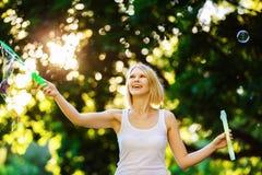 La muchacha feliz alegre con sonrisa hermosa está soplando burbujas en s Imagen de archivo