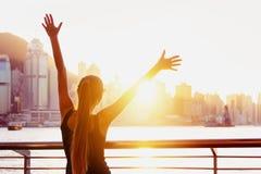 La muchacha feliz aumentó la puesta del sol Hong Kong de las manos imagenes de archivo