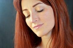 La muchacha feliz blanca con el pelo rojo y los ojos verdes con extensiones de la pestaña en fondo oscuro con los ojos se cerró fotografía de archivo