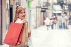 La muchacha feliz camina a través de la calle después de hacer compras Ella que se sostiene imágenes de archivo libres de regalías