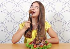 La muchacha feliz come la albóndiga Fotos de archivo