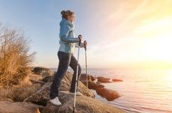 La muchacha feliz con caminar se pega en un lago en las rocas Estonia Fotos de archivo