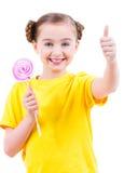 La muchacha feliz con el caramelo coloreado que muestra los pulgares sube la muestra Imagen de archivo