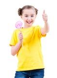 La muchacha feliz con el caramelo coloreado que muestra los pulgares sube la muestra Fotos de archivo libres de regalías