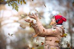 La muchacha feliz con el casquillo rojo camina en parque del otoño y coge el fal Fotos de archivo