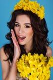La muchacha feliz con el ramo de narciso amarillo florece Fotos de archivo
