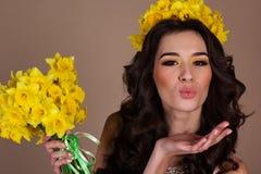 La muchacha feliz con el ramo de narciso amarillo florece Imagenes de archivo