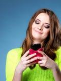 La muchacha feliz con el teléfono móvil lee el mensaje Imagen de archivo libre de regalías