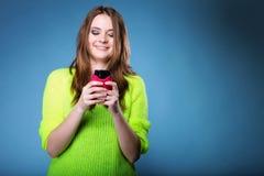 La muchacha feliz con el teléfono móvil lee el mensaje Imágenes de archivo libres de regalías