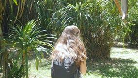 La muchacha feliz con la mochila está caminando a lo largo de selva verde y se está divirtiendo Mujer hermosa joven que va y que  imagen de archivo libre de regalías