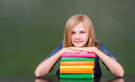 La muchacha feliz con la pila reserva cerca de la pizarra verde vacía Fotografía de archivo