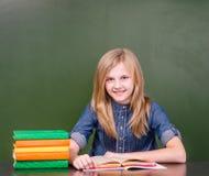 La muchacha feliz con los libros acerca a la pizarra verde vacía Imagenes de archivo