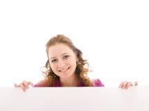La muchacha feliz con un cartel aislado en un blanco Imágenes de archivo libres de regalías
