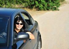 La muchacha feliz conduce su coche en el campo Fotografía de archivo libre de regalías