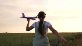 La muchacha feliz corre con un avión del juguete en un campo de trigo los ni?os juegan el aeroplano del juguete sueños del adoles metrajes