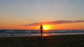 La muchacha feliz corre a lo largo de la playa hacia la agua de mar en un fondo de la puesta del sol metrajes