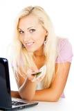 La muchacha feliz da el dinero que se sienta en un ordenador portátil Imagen de archivo libre de regalías