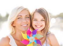 La muchacha feliz de la madre y del niño con el molinillo de viento juega Imagen de archivo libre de regalías