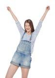 La muchacha feliz de la moda de los jóvenes en guardapolvos de los vaqueros con las manos para arriba aísla Imágenes de archivo libres de regalías