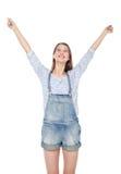 La muchacha feliz de la moda de los jóvenes en guardapolvos de los vaqueros con las manos para arriba aísla Fotos de archivo