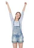 La muchacha feliz de la moda de los jóvenes en guardapolvos de los vaqueros con las manos para arriba aísla Fotografía de archivo