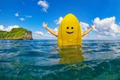 La muchacha feliz de la persona que practica surf se sienta en la tabla hawaiana amarilla con la cara sonriente Foto de archivo