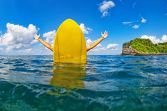 La muchacha feliz de la persona que practica surf se sienta en la tabla hawaiana amarilla en el océano imagen de archivo libre de regalías
