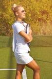La muchacha feliz de los deportes se coloca con la estafa en corte en el día de verano soleado Fotos de archivo