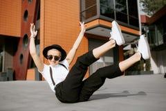 La muchacha feliz de moda del inconformista con el sombrero y las gafas de sol se divierten que se sienta en el piso Concepto de  Fotos de archivo libres de regalías